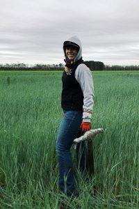 Young woman wearing a hood in an open field