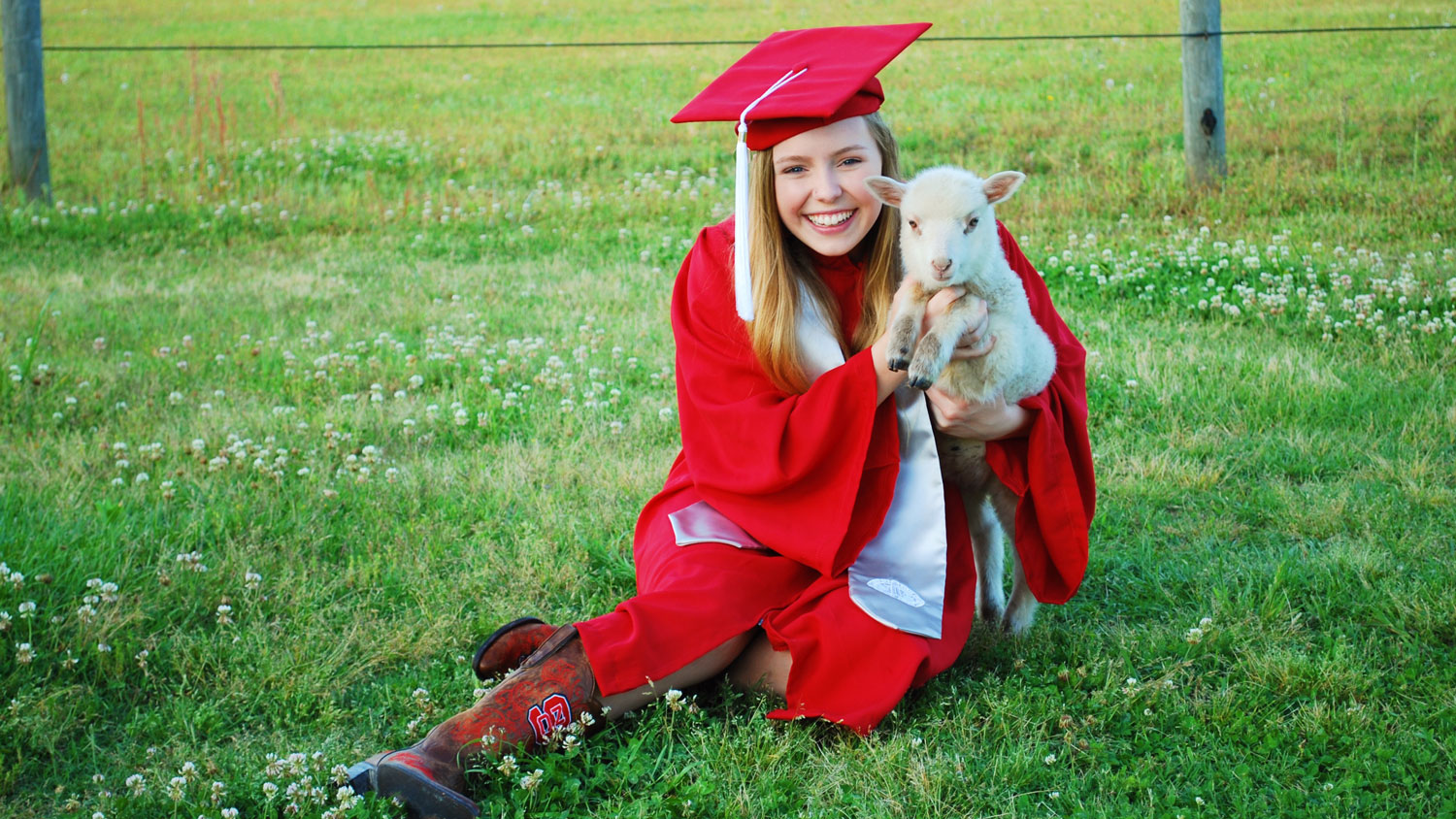 Young woman in a red cap and gown holding a goat