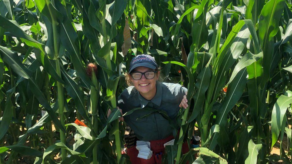 Woman smiling in field of corn.