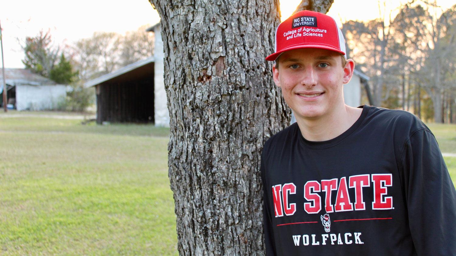 A young man standing next to a tree on a farm wearing NC State apparel.