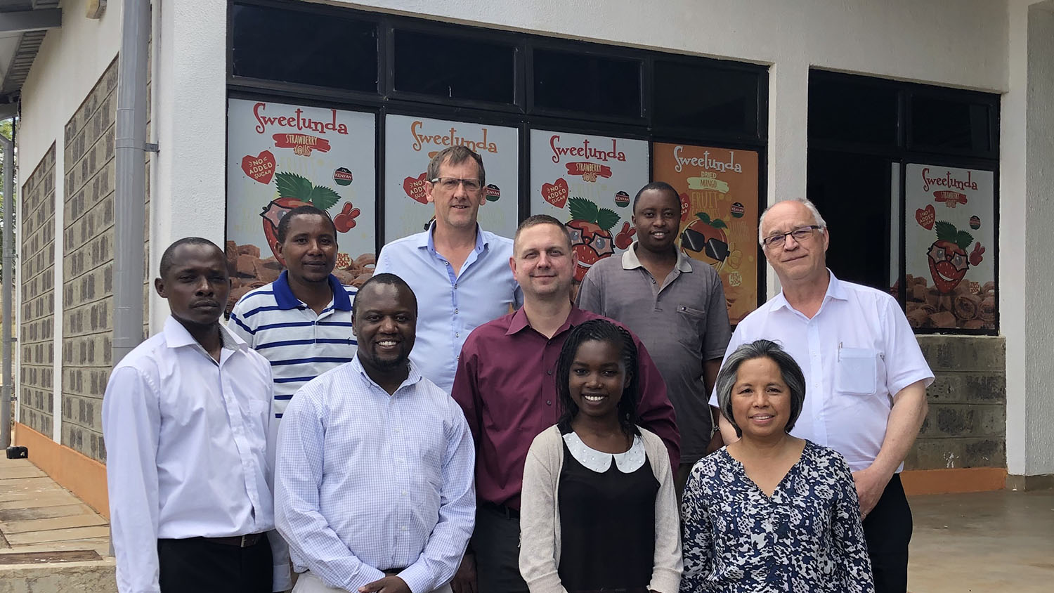 A group photo of nine individuals, African and Caucasian in front of a store front in Kenya.