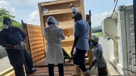 A group of five men unloading a wooden crate.