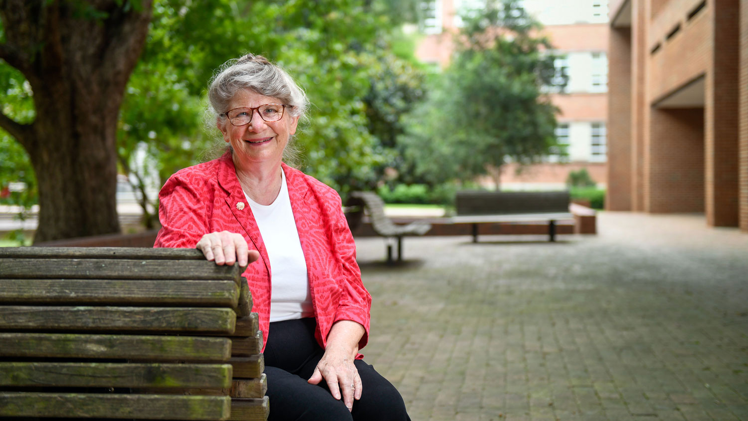 An older woman wearing glasses sitting on a bench