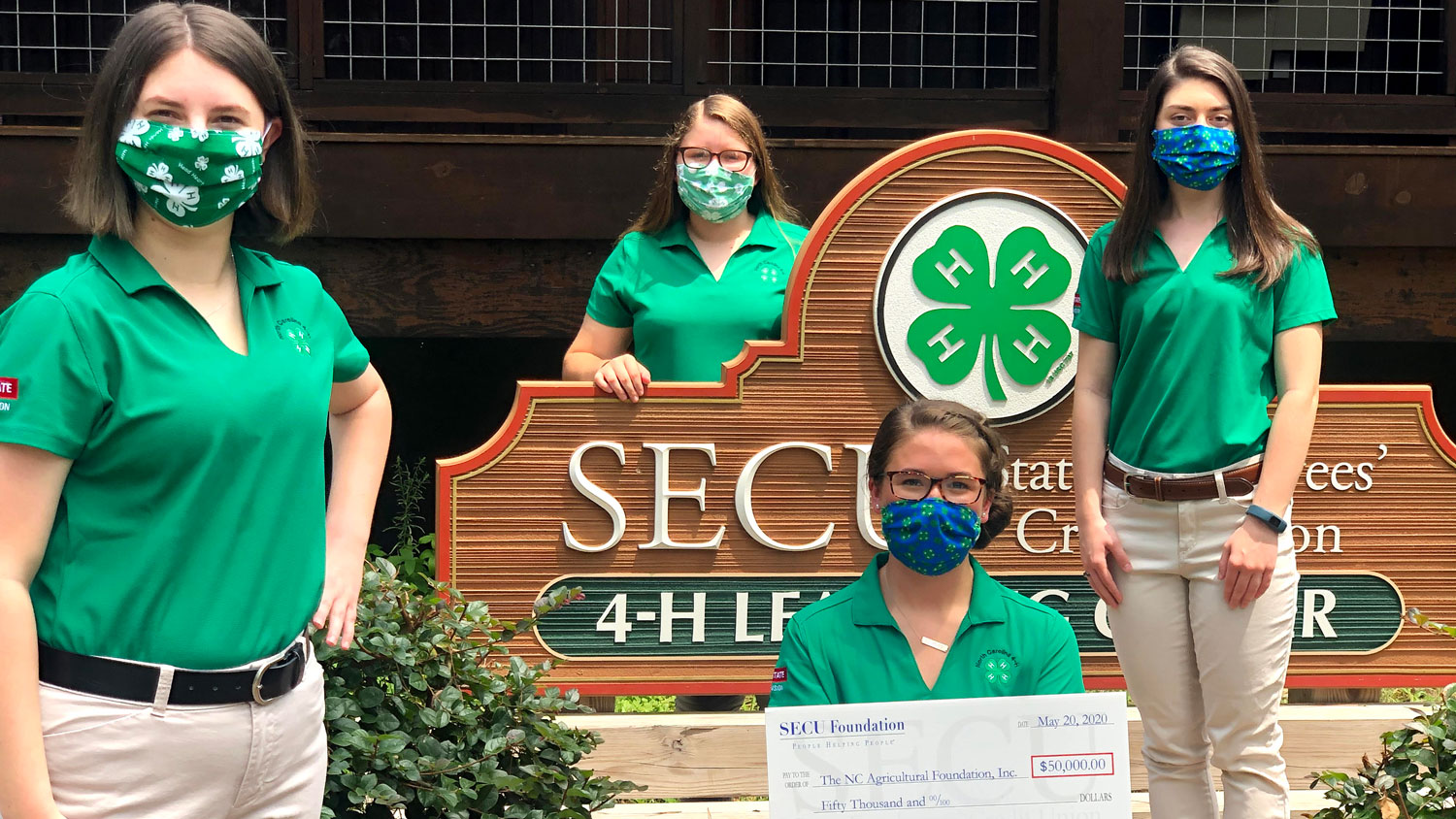 Group of 4-H staff members holding a check from SECU Foundation for $50,000