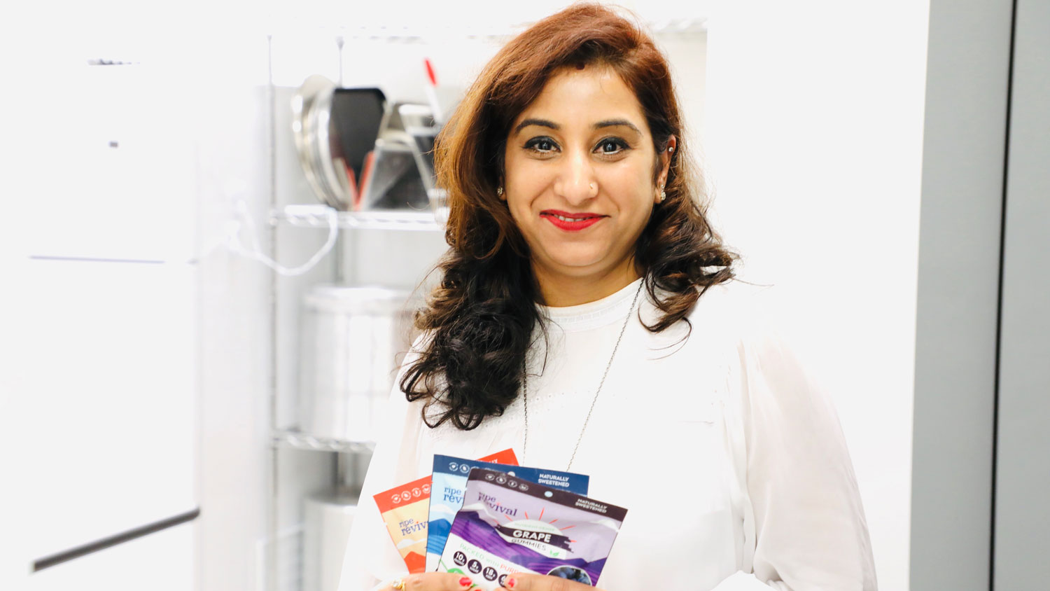 An Indian woman holding three packages of gummies