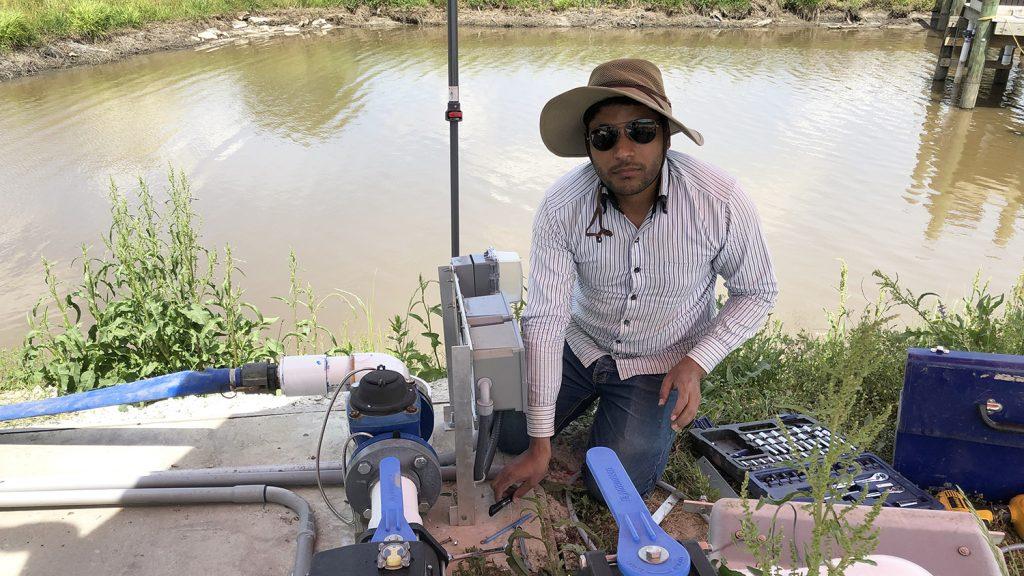 Man squatting near equipment near a farm pond