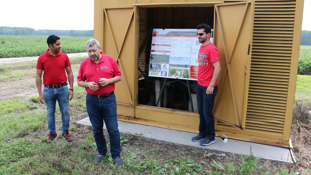 Three men in a farm field making a poster presentation. The poster is in a metal structure.