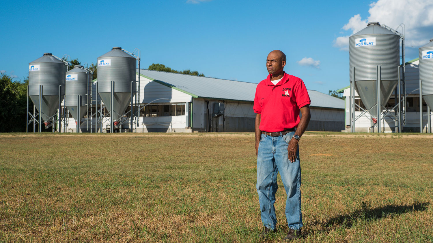 A Black man standing in a filed in front of his farm.