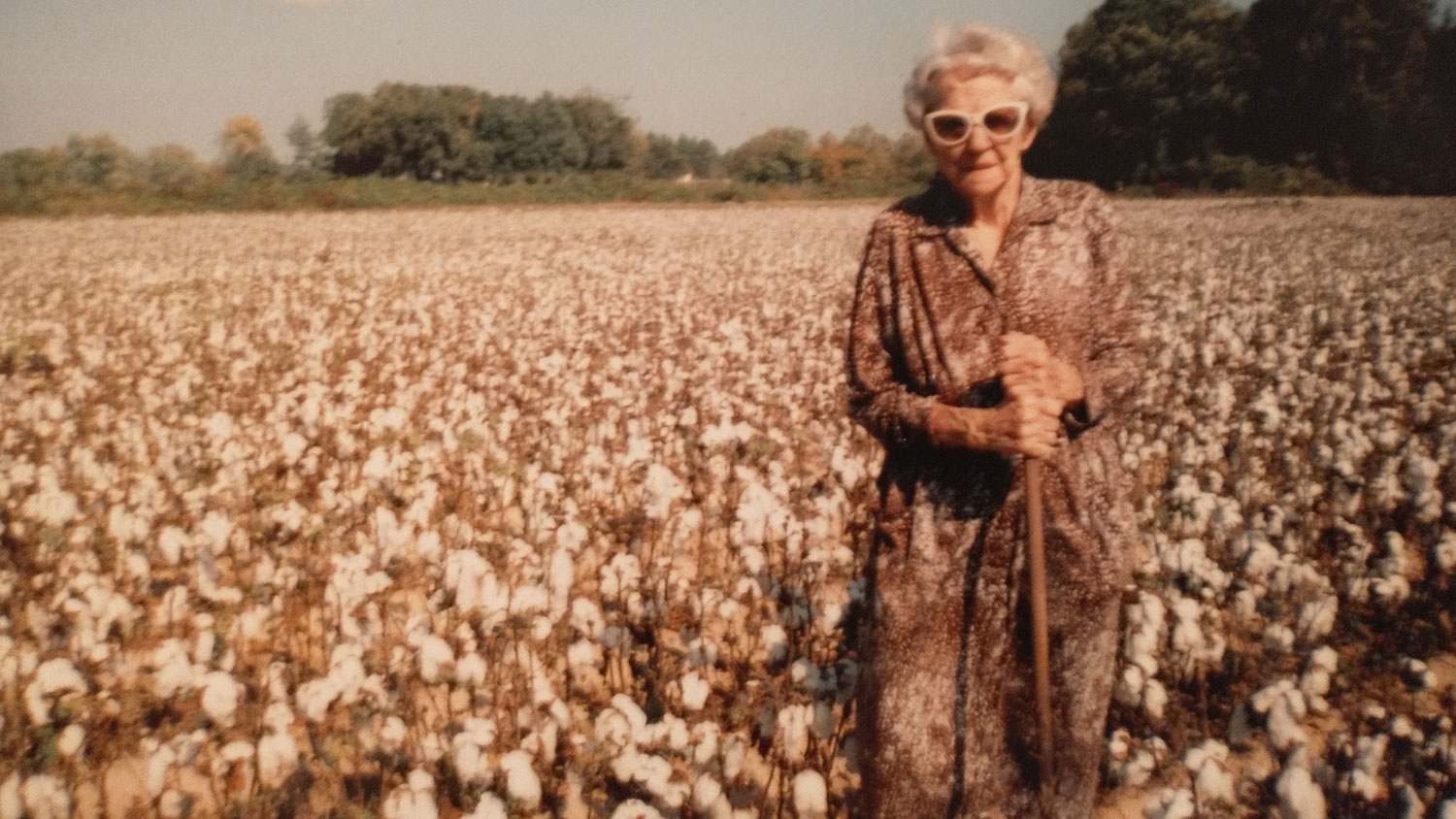 Photo from the 1980s of an older white woman standing in front of a cotton field.
