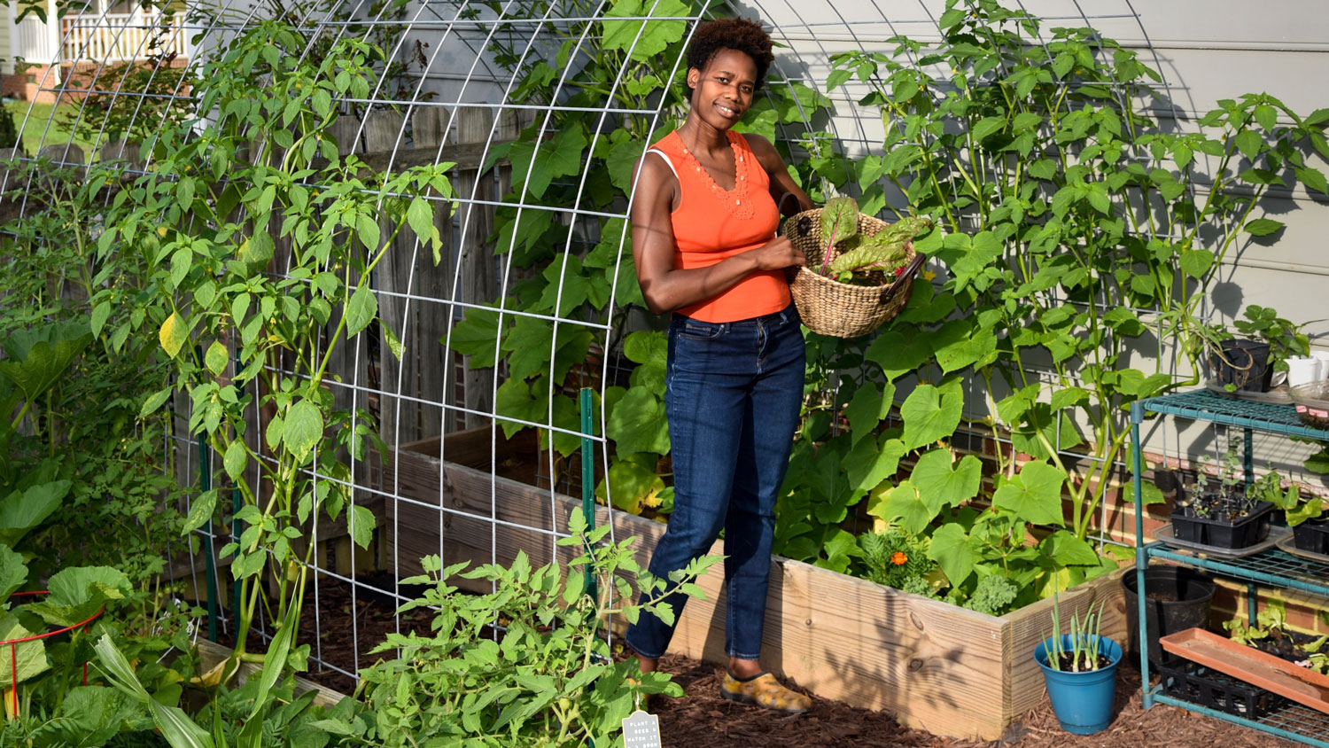 A young black woman in a garden holding a basket