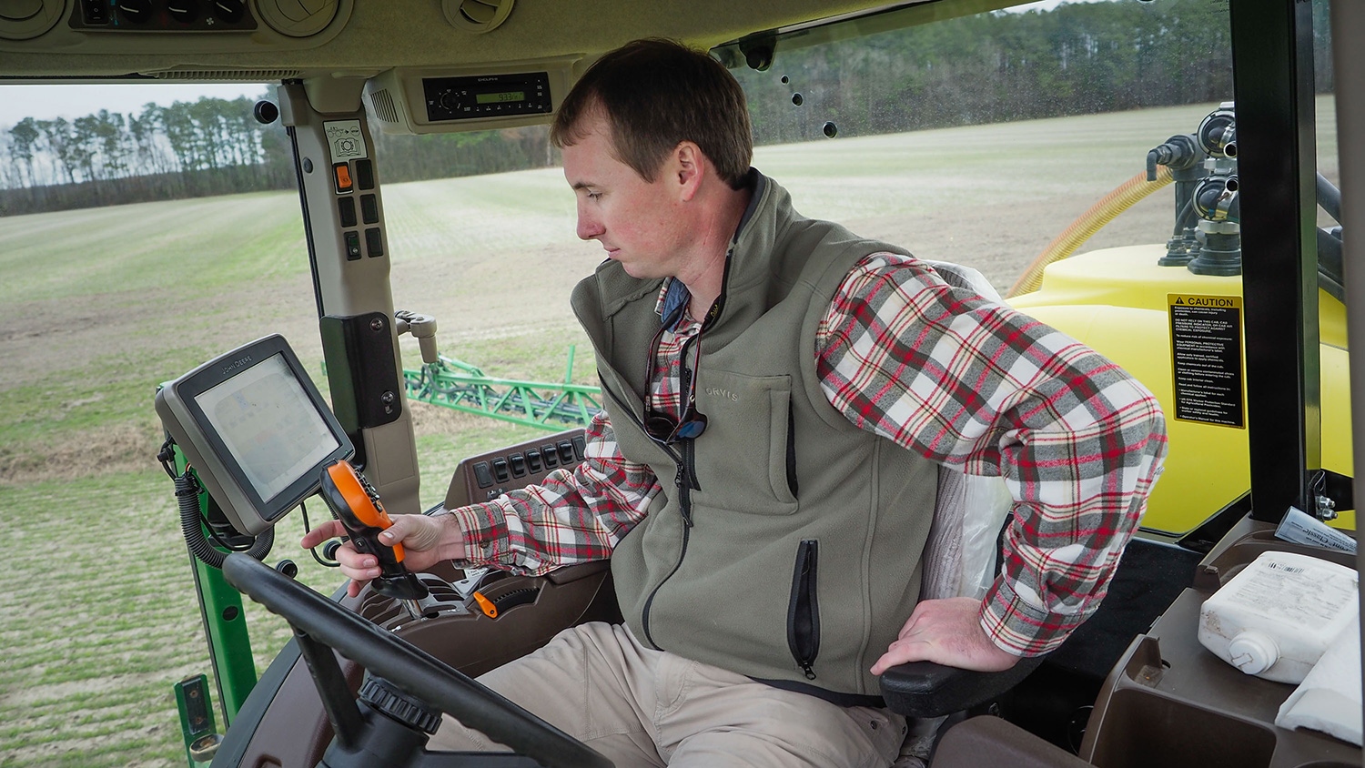 A young man sitting in a tractor looking at farming data.