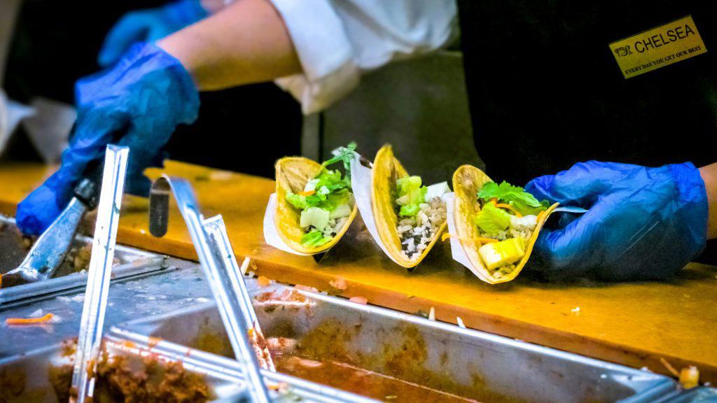 A restaurant server making three tacos