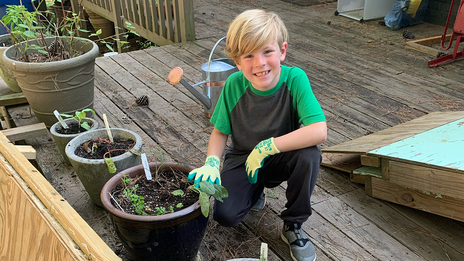 Seven-year-old boy poses with the container garden on his deck