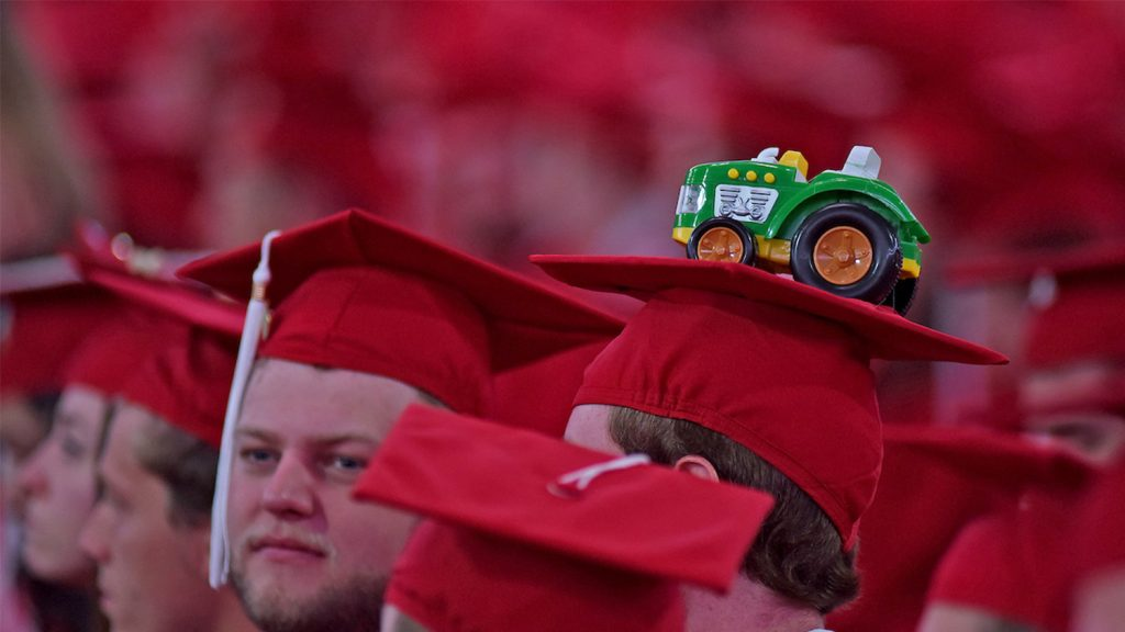 red graduation caps with a tractor on top of one cap