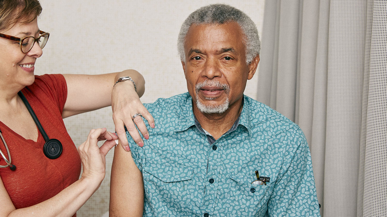 An elderly Black man receiving an injection in his arm