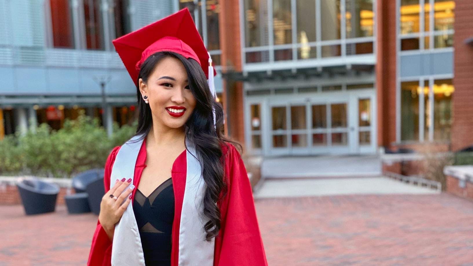 Asian woman in red graduation cap and gown