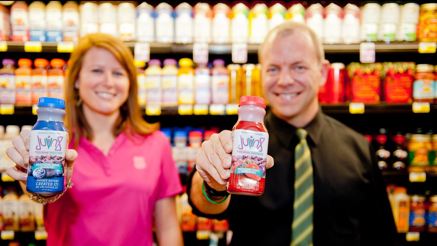Student and professor holding juice bottles in a grocery store aisle