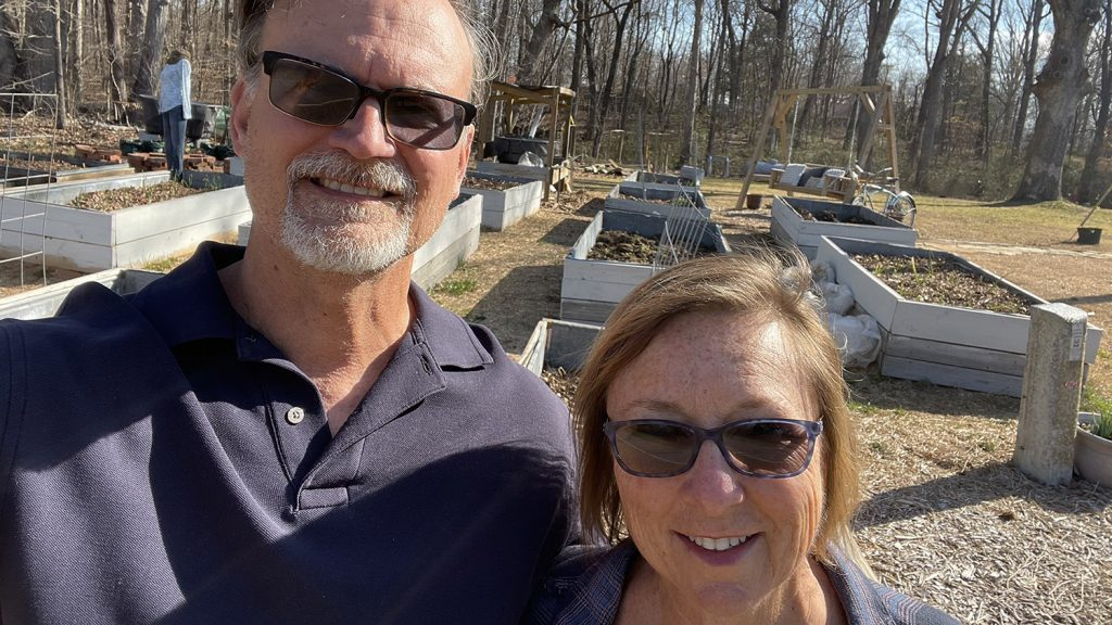 Man and woman in front of several raised beds for growing vegetables and fruit.