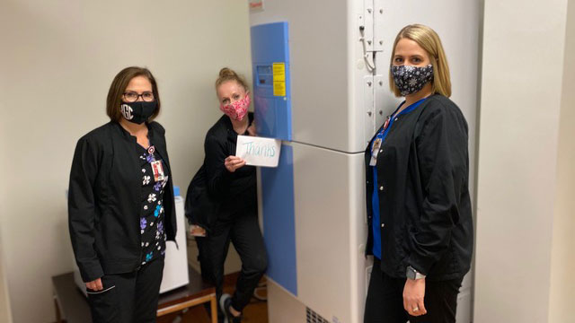Three female nurses standing next to a freezer.