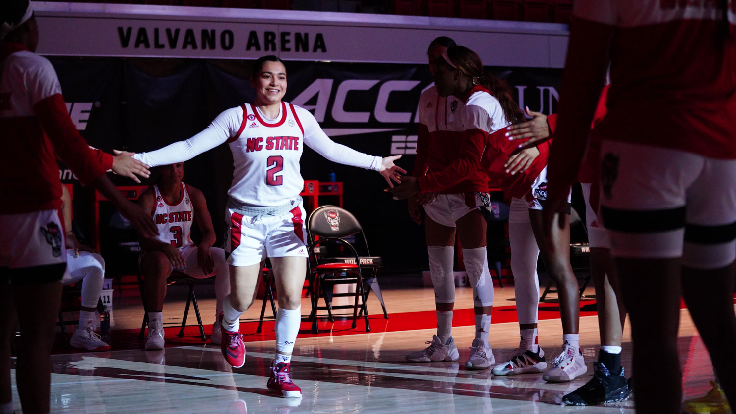 Raina Perez walking onto the basketball court before a game.