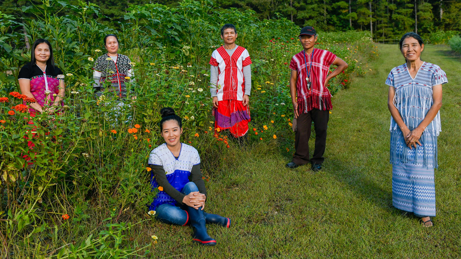 A group of Myanmar refugees standing in a garden