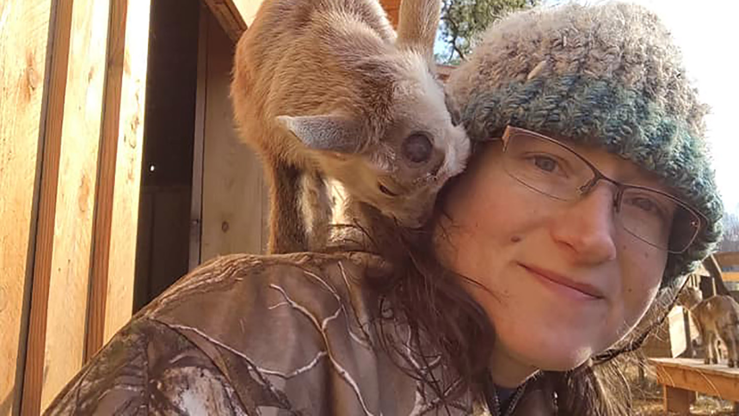 Woman with small goat on her shoulder