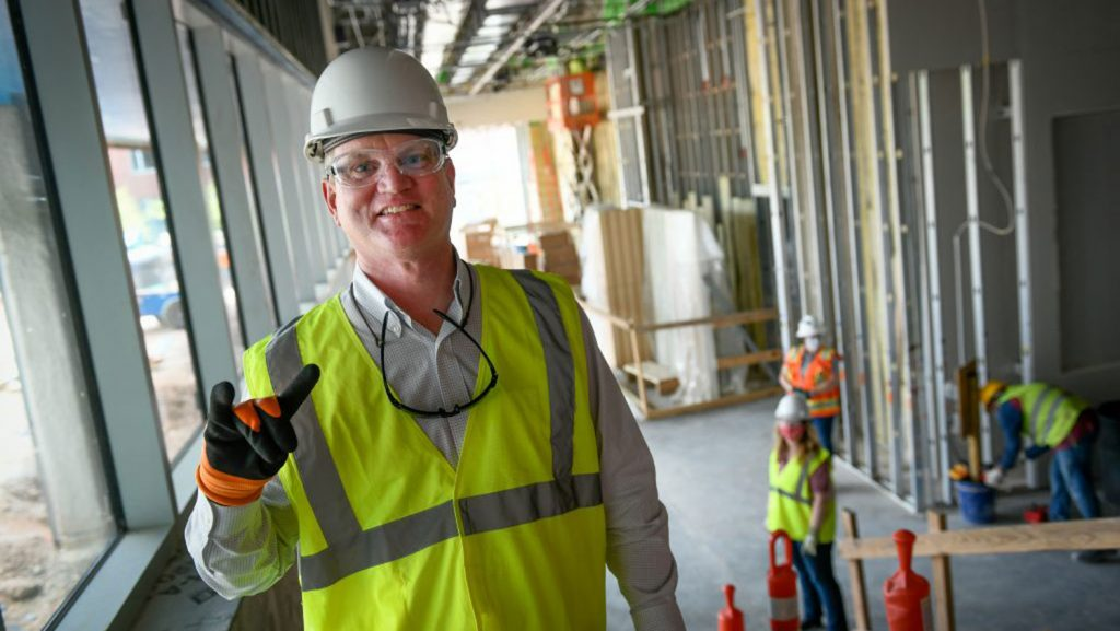 Jim Whitehurst wearing a hard hat at a construction site.