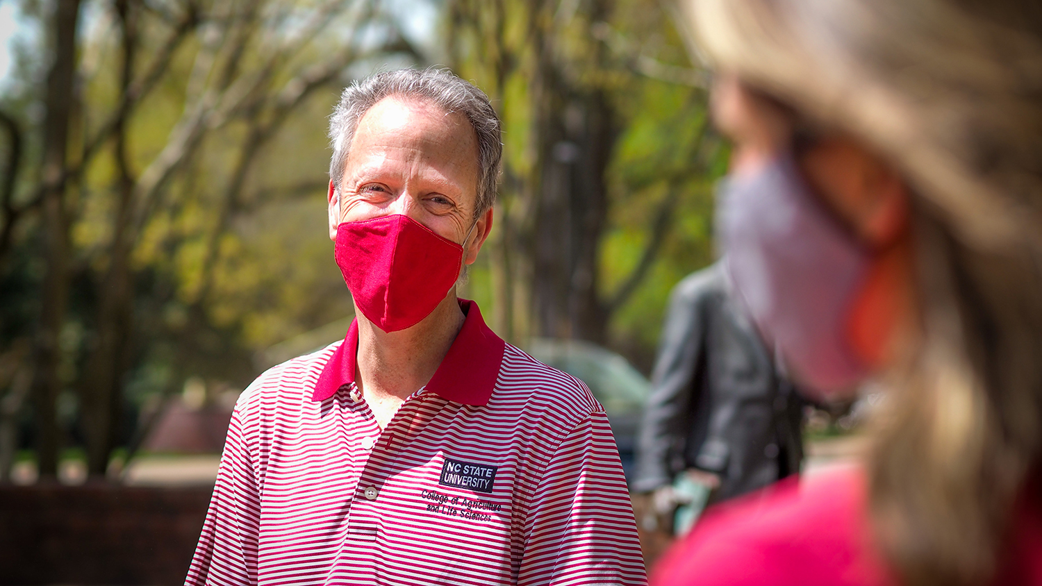 Man with mask talks to student outdoors