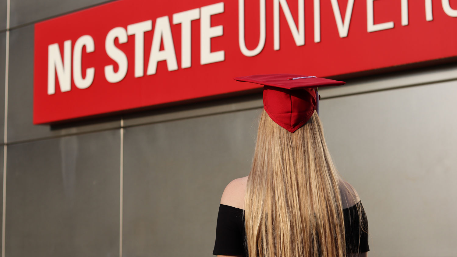 A young woman looking away wearing a red graduation cap