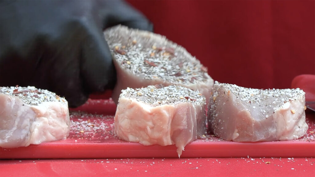 a hand seasoning a piece of meat