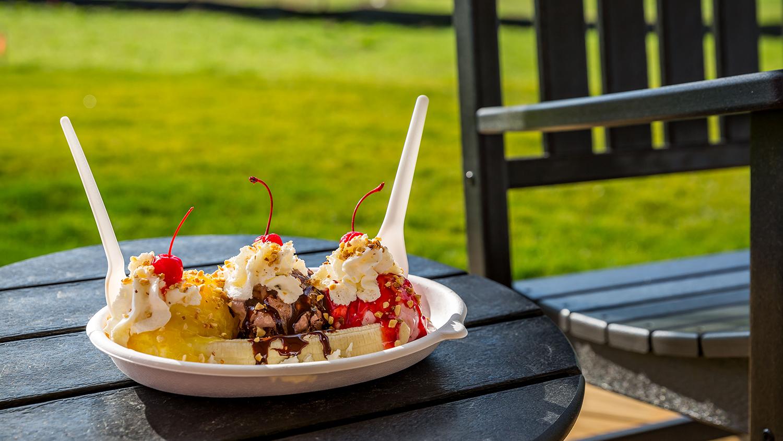 A banana split sundae with cherries and whipped cream