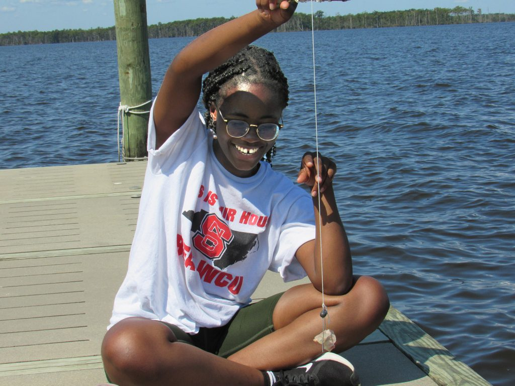 Senior Selma O. (dual degree in Biochemistry and Spanish) checks her crabbing line at the Jefferson Scholars annual fall retreat, held this year at the 4-H Center in Columbia, NC.