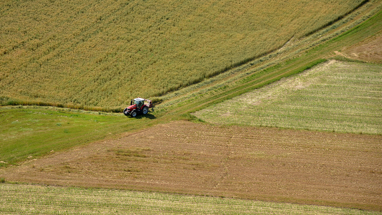 an aerial shot of a tractor in a large field