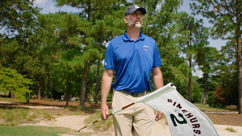 John Jeffreys holding a hole flag at Pinehurst's course No. 2