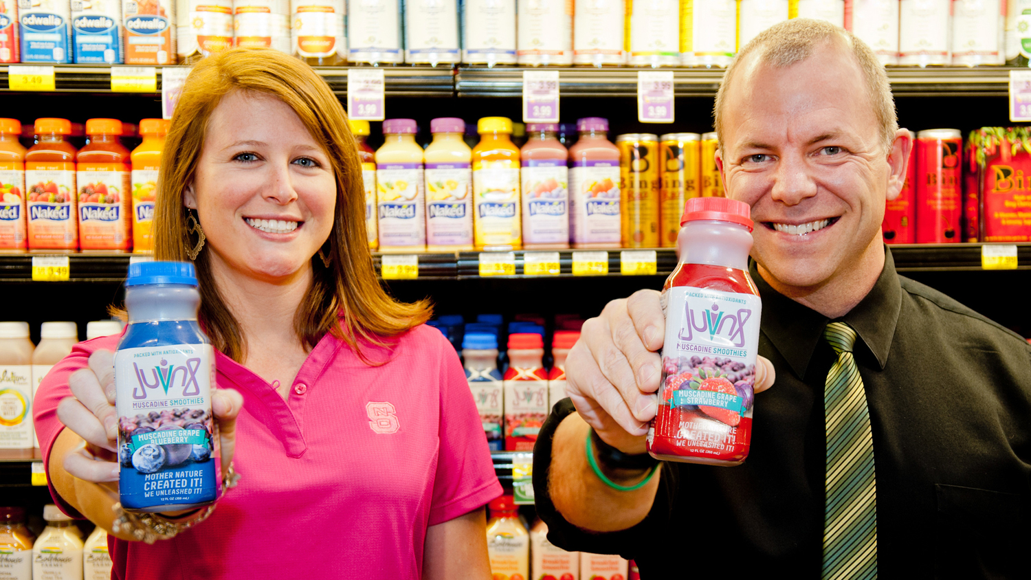 A student and a faculty member showing off a juice product in a grocery store based off of NCState research.