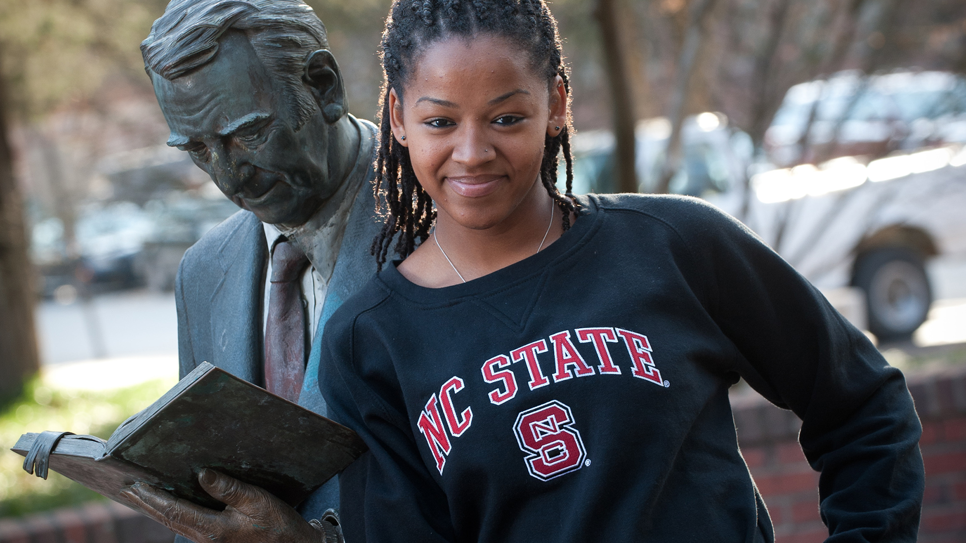 Female student with statue on campus.
