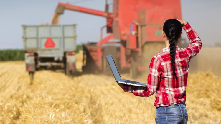 Farmer with laptop looks at farming equipment