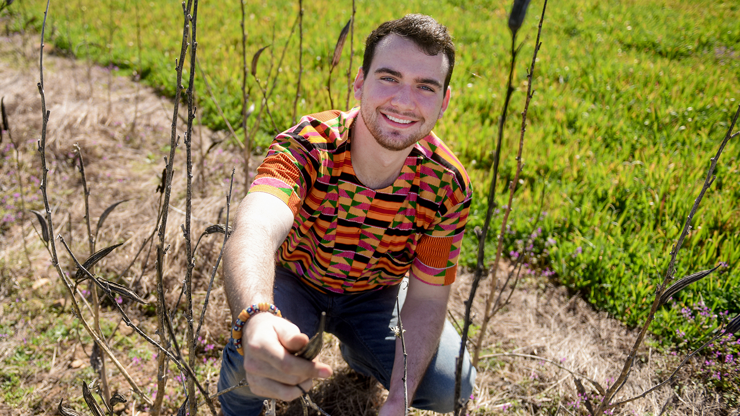 Male student helping build a farm for a school in Africa.