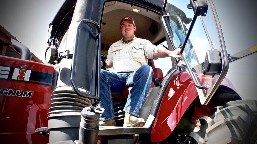 CALS grad Brandon Batten sitting on a tractor