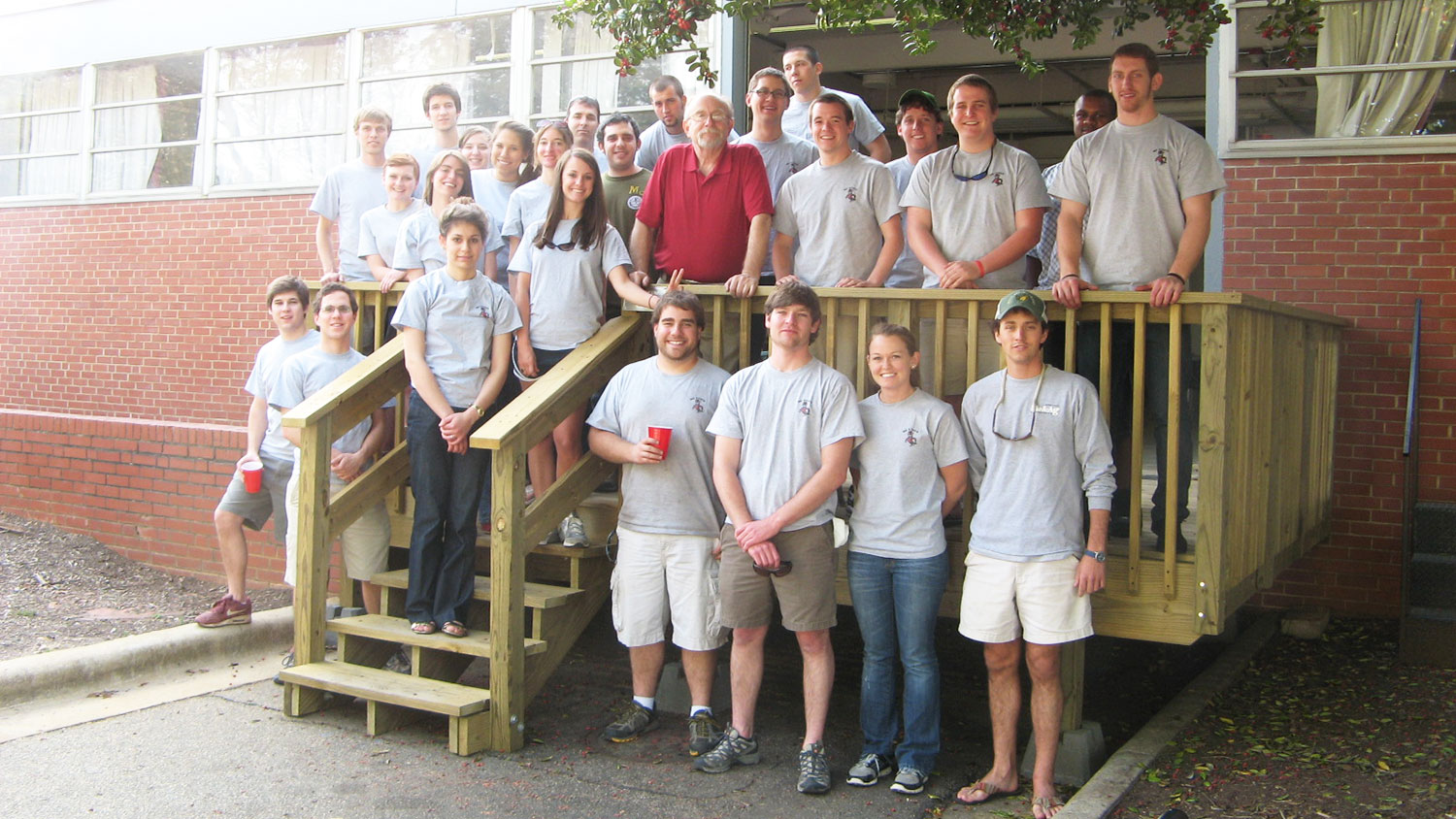 Mike Boyette surrounded by Senior Design Program students on the Weaver Labs porch.