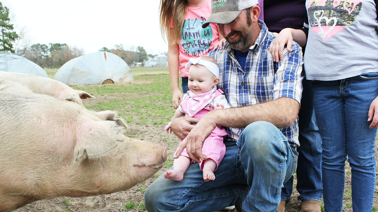 man holding baby with pig