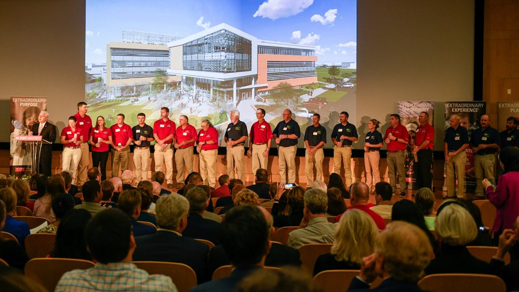 On a stage in front of a big architectural rendering, North Carolina agricultural research station superintendents pose with soil they brought from 18 stations.