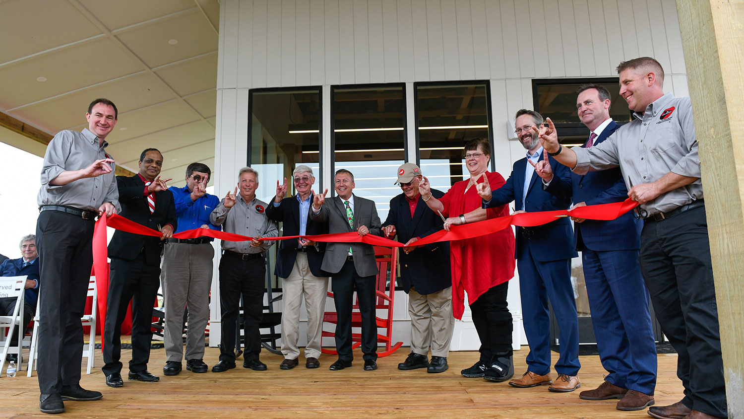 Dean Linton (center) and others holding a ribbon at the new Howling Cow Dairy Education Center and Creamery.