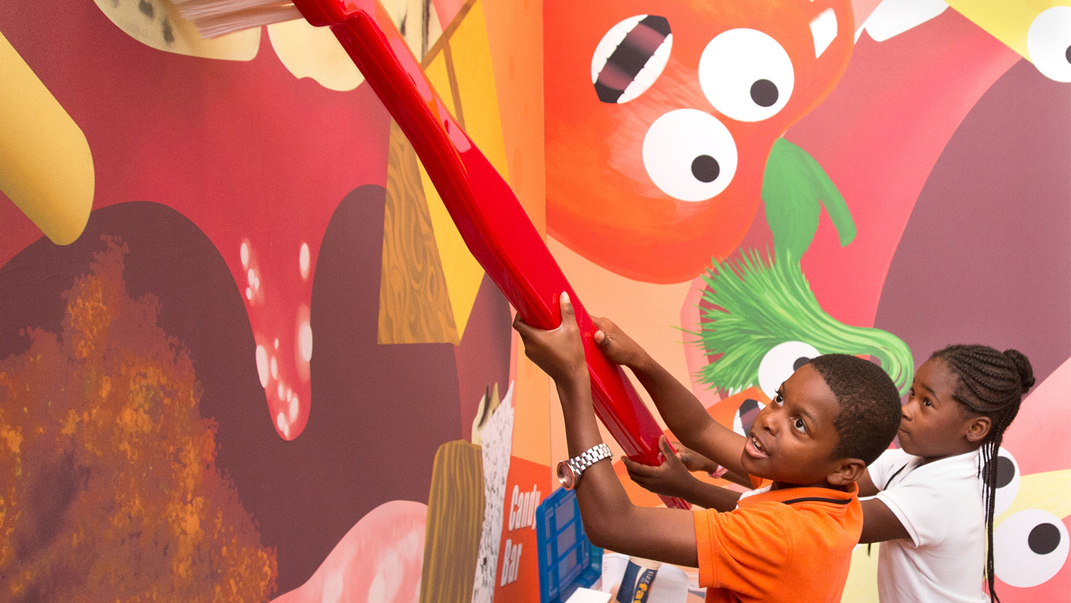 A boy and girl play with a giant toothbrush at an interactive oral health display.