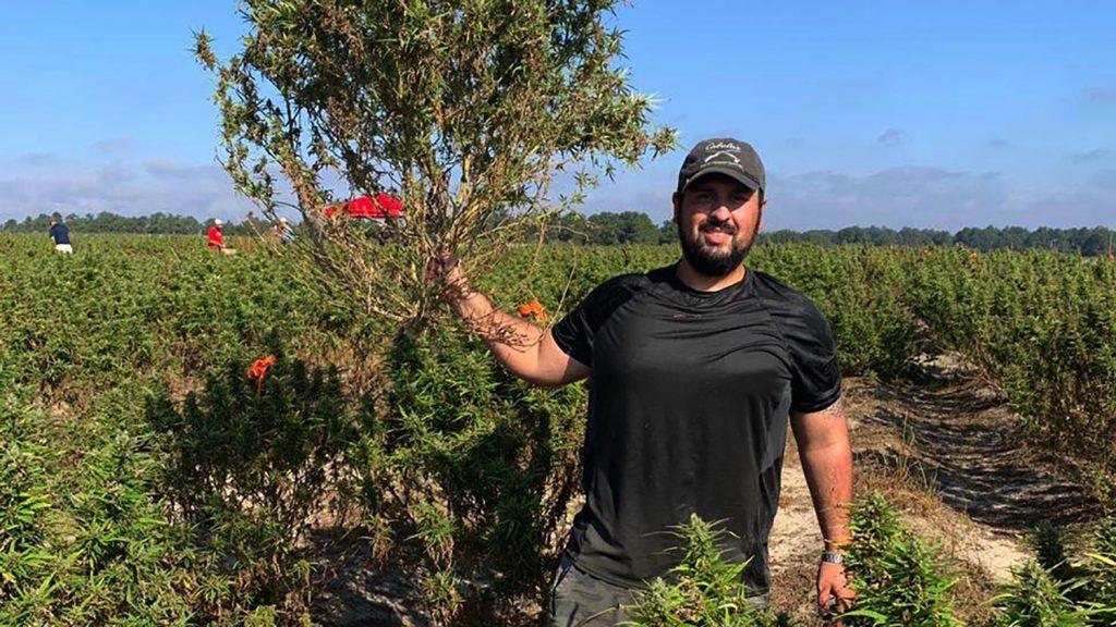 Man in cap holds up a North Carolina hemp plant.