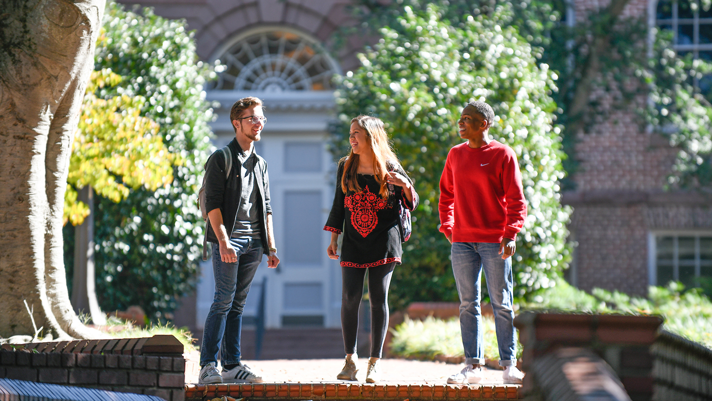 Three students talking outside on sidewalk