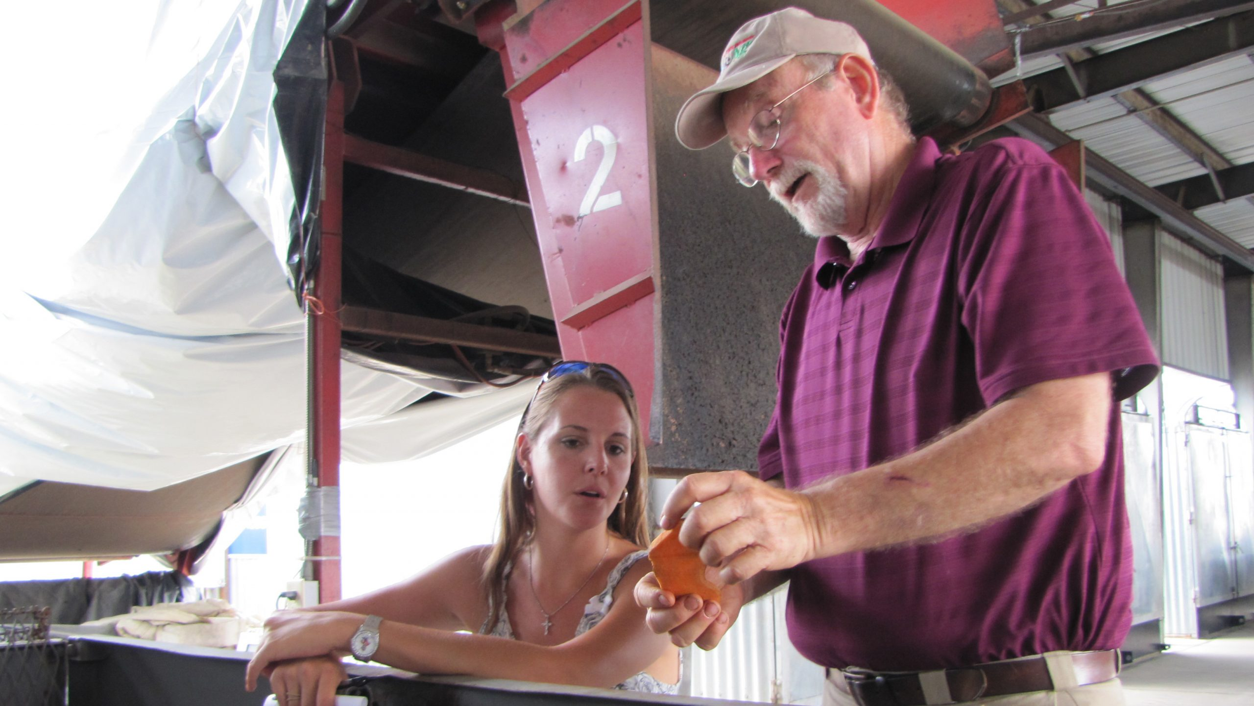 With woman looking on, man examines a peeled sweet potato