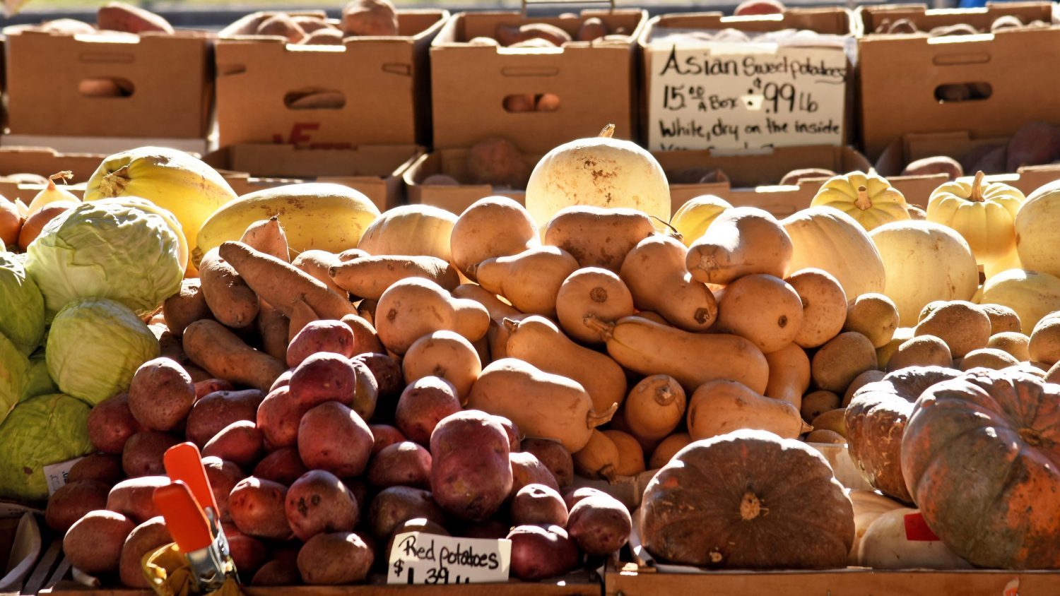 Grounds and other produce displayed at a farmers market stand