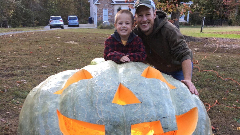 Man and boy pose with a giant jack-o'-lantern.