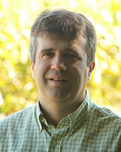 Chris Reberg-Horton in front of trees.